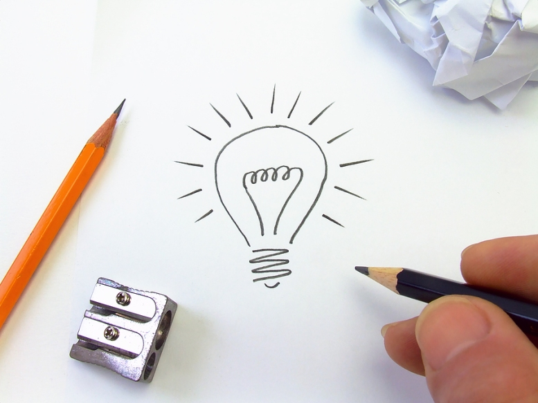 Image of a hand drawing a lightbulb in pencil to represent an idea