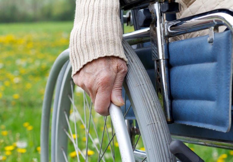 A closeup of a woman's hand on her wheel chair spokes. A grassy field fills the background.